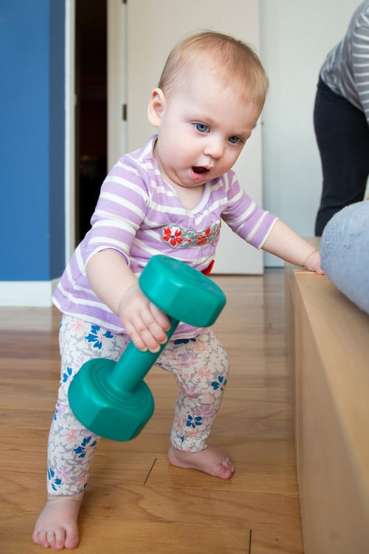 A Toddler Lifting a Dumbbell