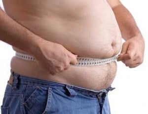 An Overweight Man With a Tape Measure Around His Waist