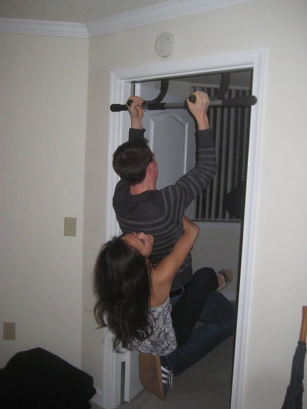 A Woman Hanging onto the Waist of a Man Performing Pull Ups