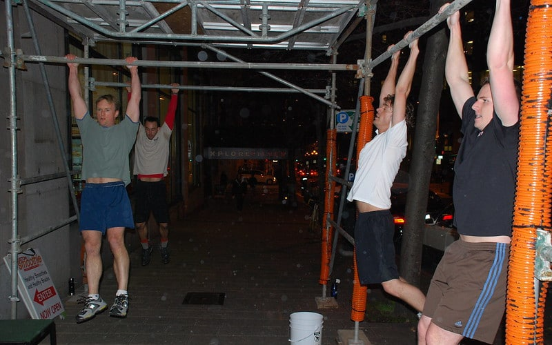 A Group of Men Hanging From Scaffolding Poles About to Perform Pull Ups
