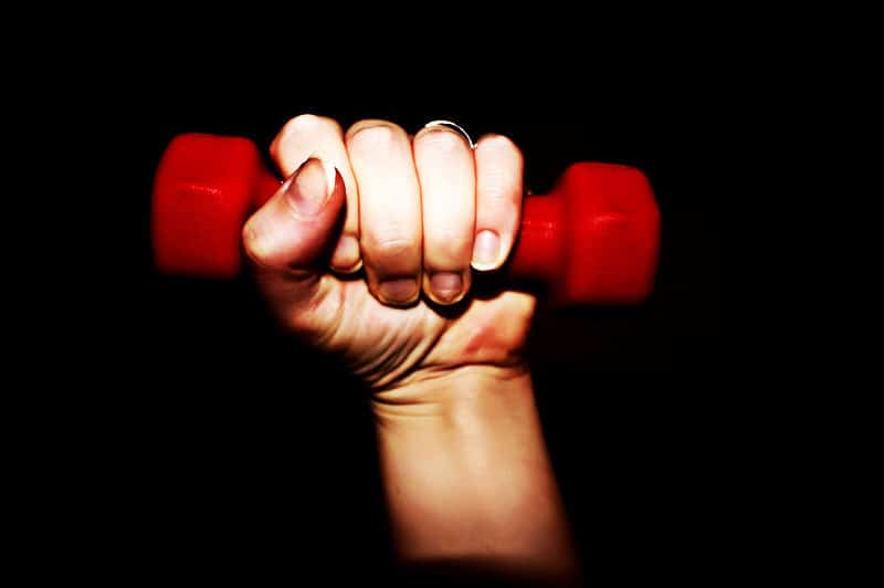 A Hand Gripping a Small Red Dumbbell