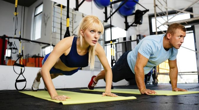 A Man and a Woman Performing Push Ups