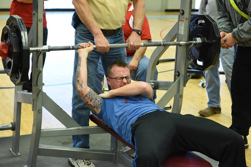 A Man Holding His Shoulder in Pain After Performing a Bench Press