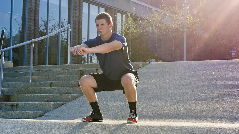 A Man Performing a Bodyweight Squat