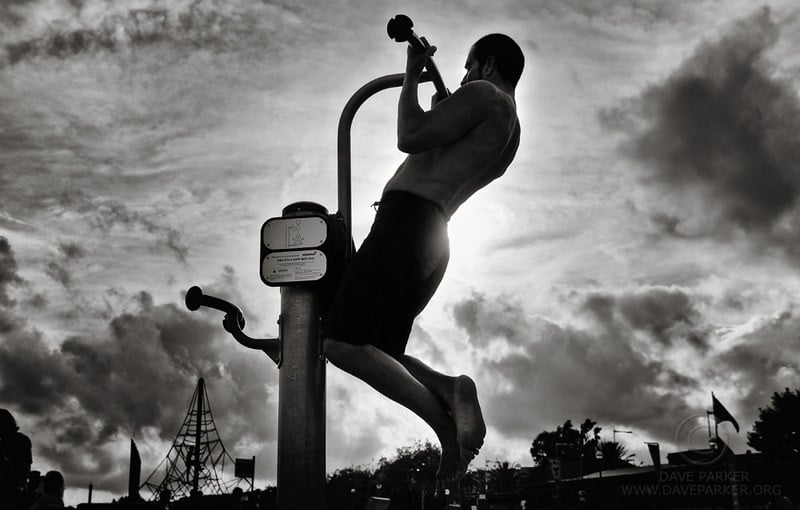 A Man Performing Pull Ups on Barcelona Beach at Dusk