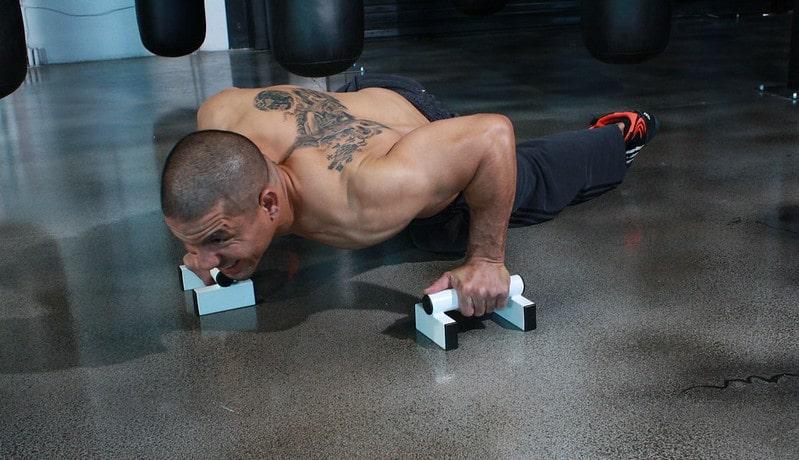 A Man Performing Push Ups With Push Up Bars
