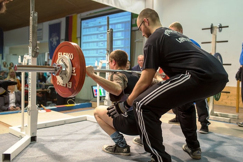 A Man Performing the Barbell Squat With Someone Standing Behind Him in Support