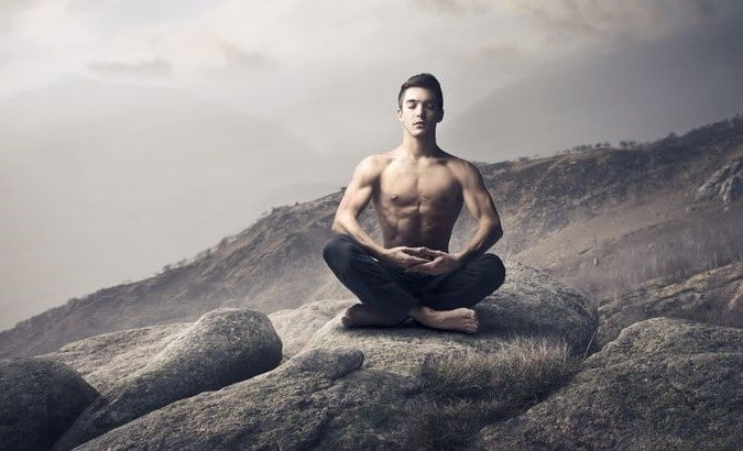 A Man Sitting in a Yoga Pose and Meditating