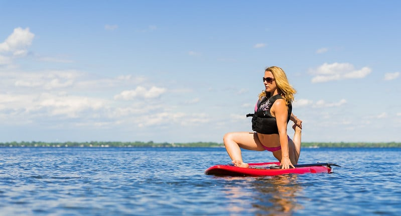 A Woman Doing a Hip Flexor Stretch on a Surfboard in the Middle of the Sea