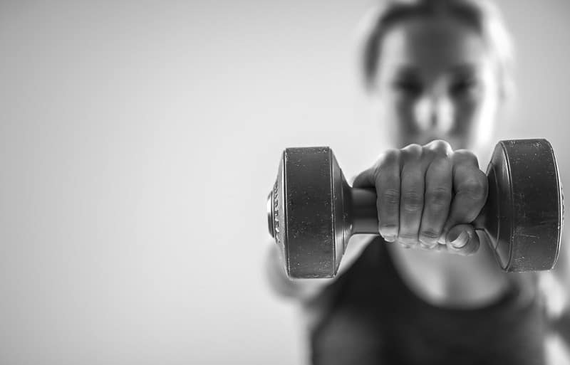 A Woman Holding a Dumbbell in Her Outstretched Hand