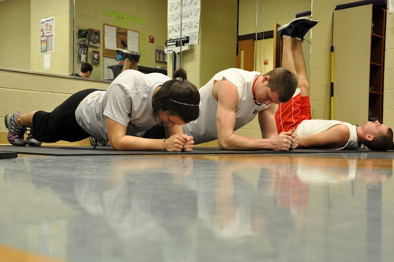 Three People Performing Ab Exercises Including Planks