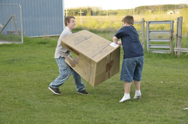 Two Boys Carrying a Large Box