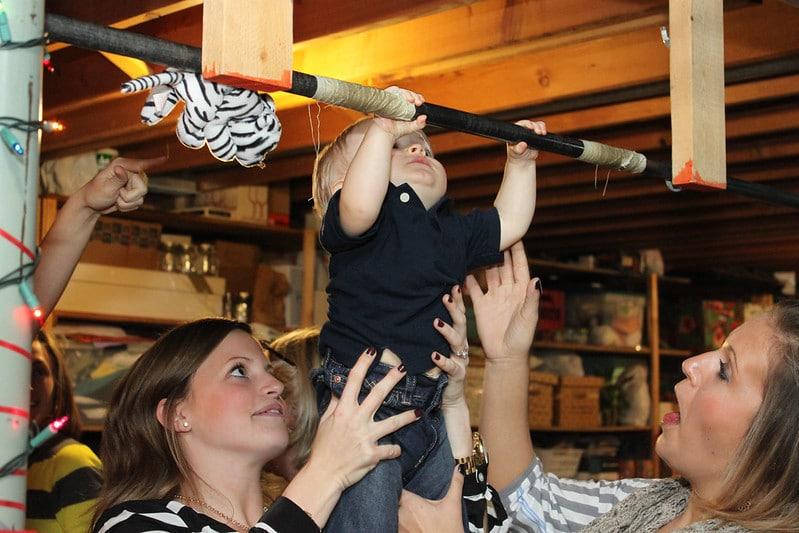 A Baby Holding Onto a Bar While Two Women Hold Him in Place