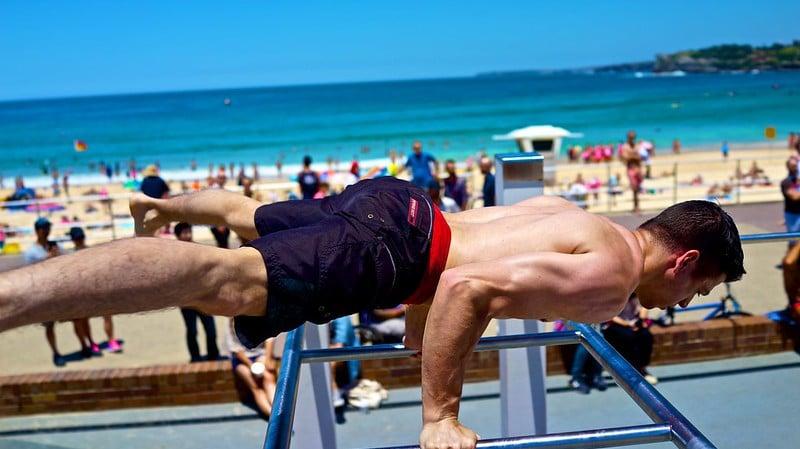 A Man Balancing on Workout Apparatus at the Beach