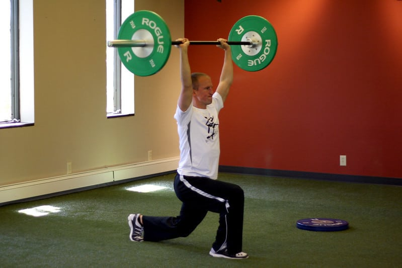 A Man Doing Overhead Barbell Lunges