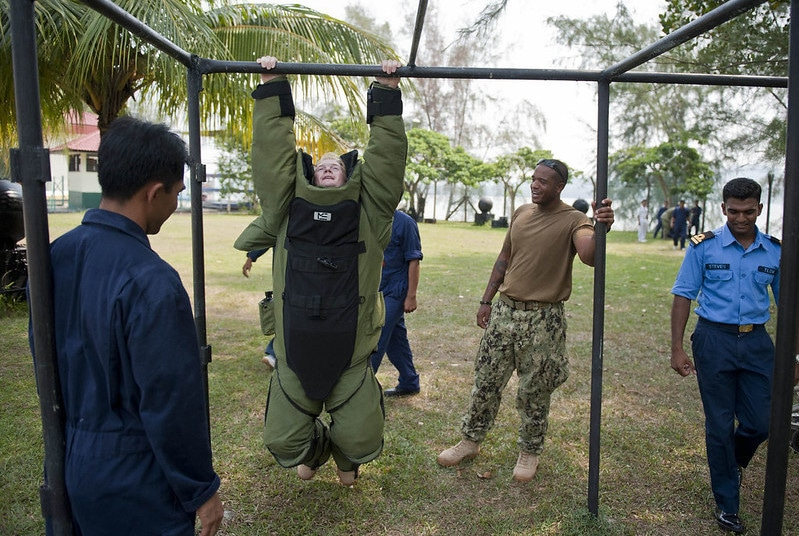 A Man in a Heavy Suit Performing Pull Ups