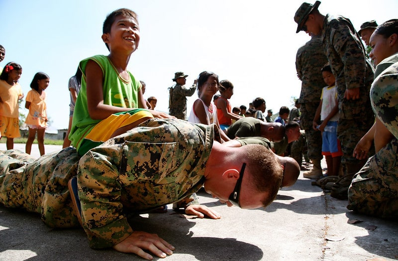 A Marine Doing Push Ups While A Boy Sits on His Back
