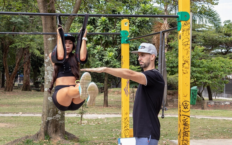 A Personal Trainer Helping a Woman do Hanging Leg Raises