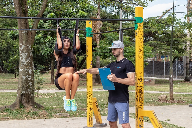 A Personal Trainer Showing a Woman How to Do Hanging Knee Raises
