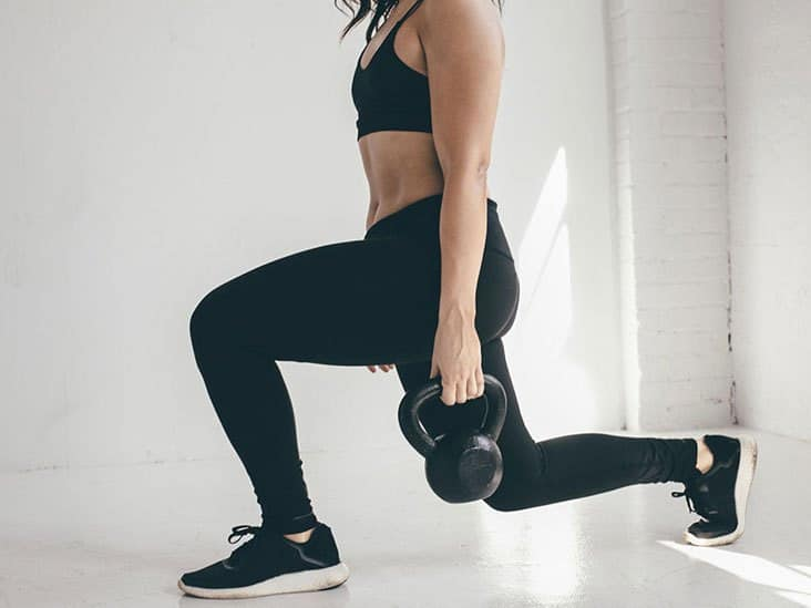A Woman Doing Kettlebell Lunges