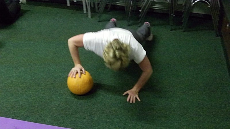 A Woman Doing Push Ups With One Hand on a Medicine Ball
