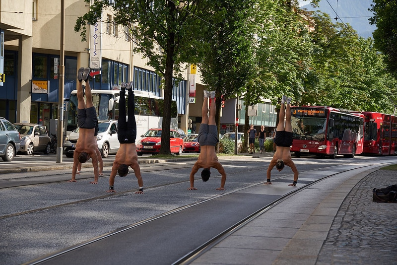 Four Men Doing Handstands in the Street