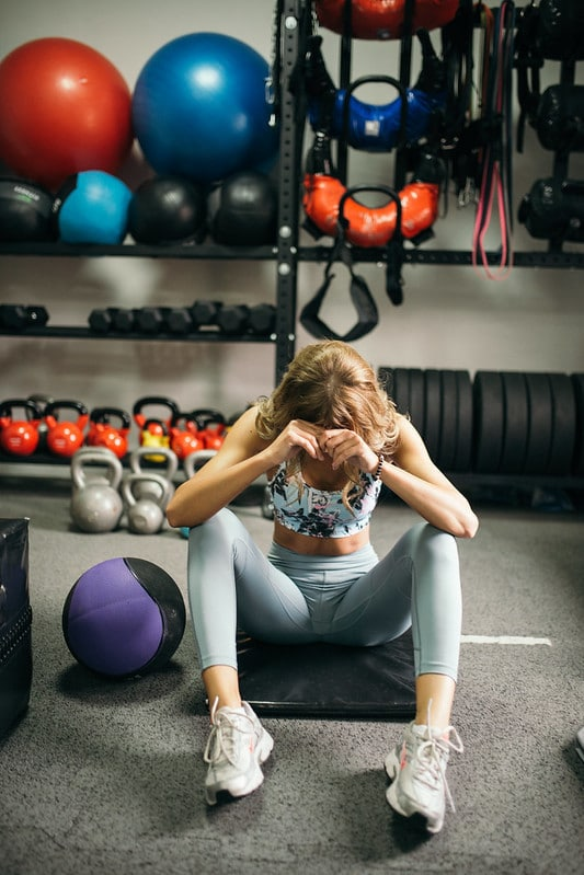 A Woman Sitting on a Gym Floor, Possibly Tired After Exercise