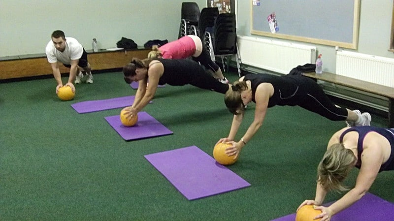 A Group of People Performing Medicine Ball Planks