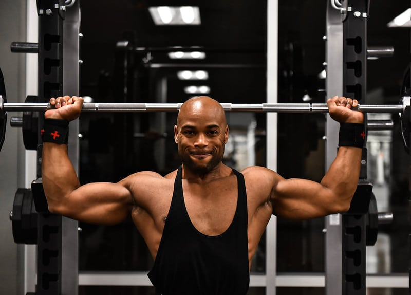 A Man Holding a Barbell in the Behind the Head Press Position
