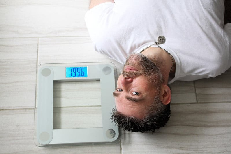 A Man Lying Next to a Set of Weighing Scales That Show 199.6