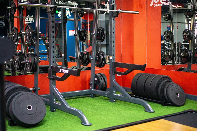 A Squat Rack With Barbell and Weight Plates
