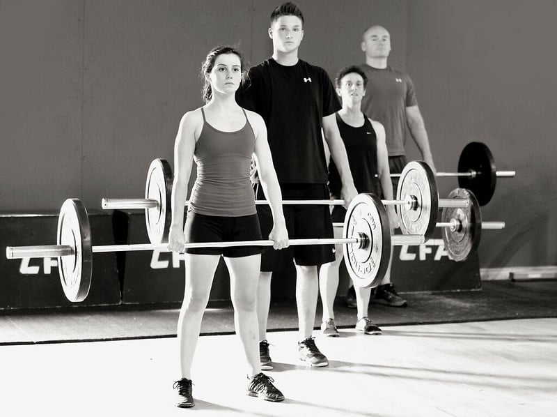 Four People Each Holding a Barbell