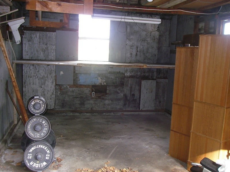 A Garage Containing Barbells, Weight Plates, and Wooden Cabinets