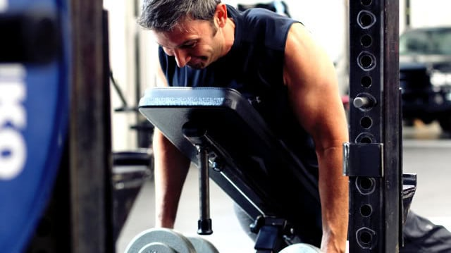 A Man Lying Face Down on an Incline Bench Holding Dumbbells in Each Hand