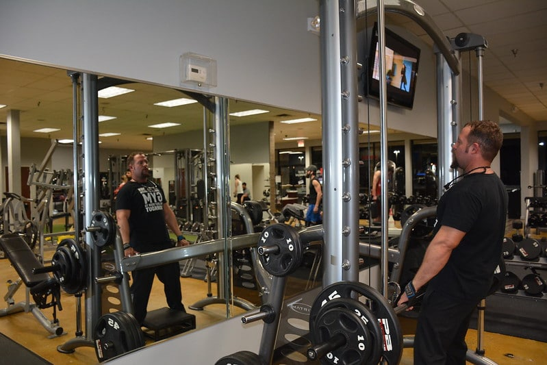 A Man Performing Deadlifts With the Smith Machine