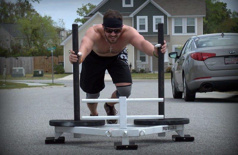 A Man Pushing a Prowler Sled Outdoors