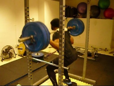 A Person Squatting in the Squat Rack with Weight Plates Under Their Heels