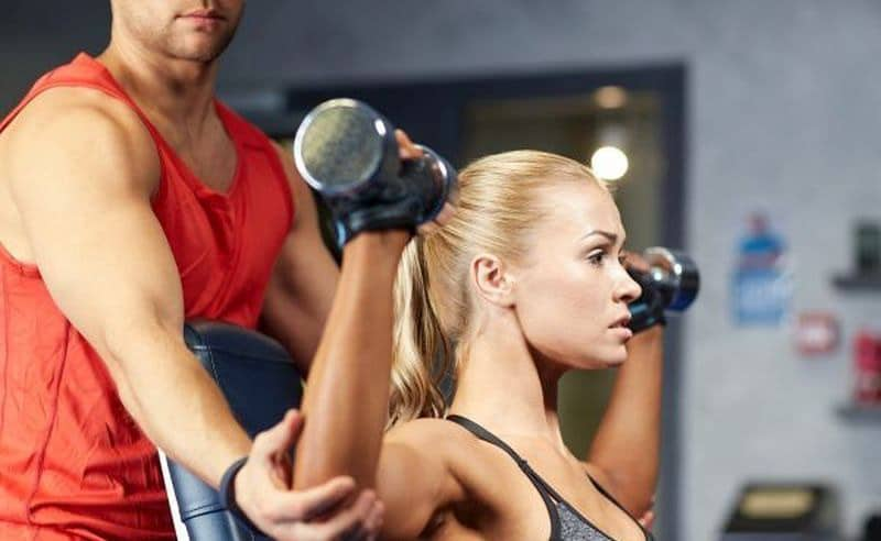 A Personal Trainer Coaching a Woman Through Seated Overhead Presses