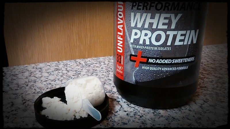 A Tub of Whey Protein With a Scoop of Protein on Top of the Lid