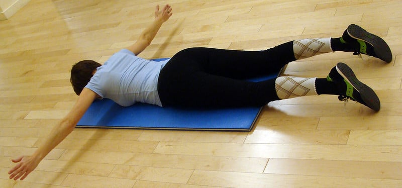 A Woman Lying on a Yoga Mat Performing a Scapular Retraction Exercise