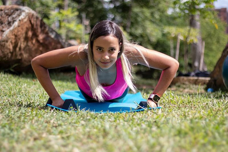 A Woman Outdoors Performing Push Ups With Her Elbows Flared Out