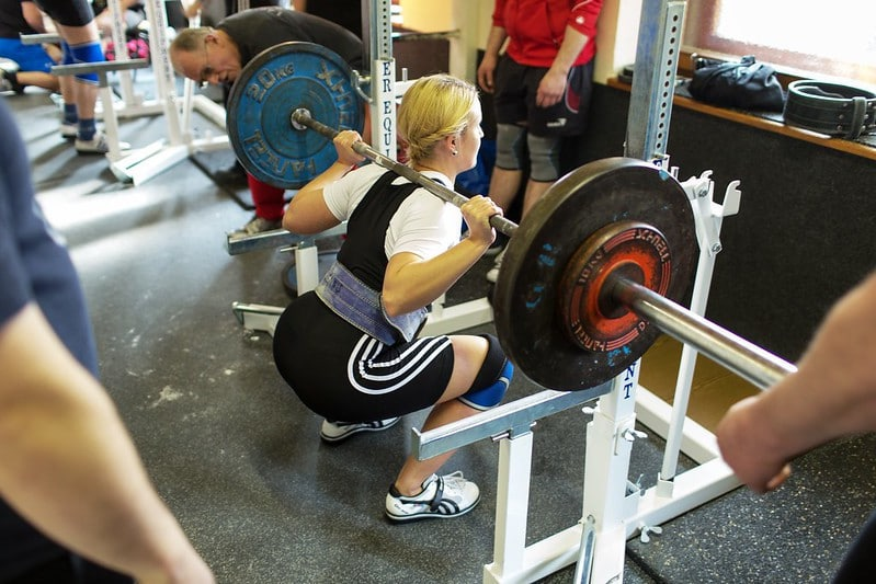 A Woman Performing a Squat in the Squat Rack