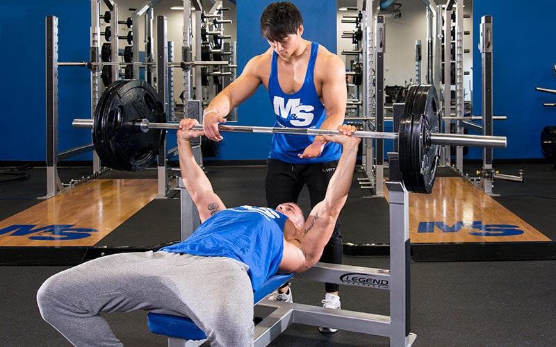 One Man Spotting Another Man Doing The Bench Press
