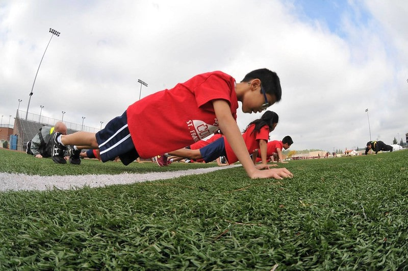 Students on a Sports Field Performing Push Ups