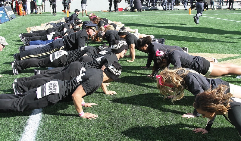 A Group of People Performing Push Ups on a Football Field
