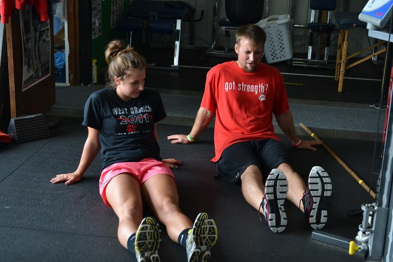 A Man and a Woman Sitting in the Floor Performing Ankle Mobility Exercises