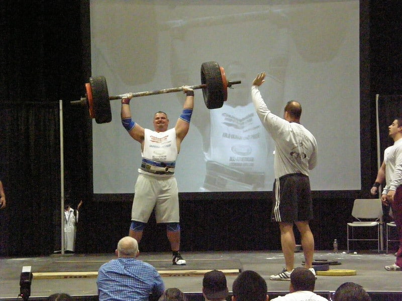 A Man at a Strongman Contest Pressing a Heavy Barbell Overhead With Judges and a Crowd Looking On