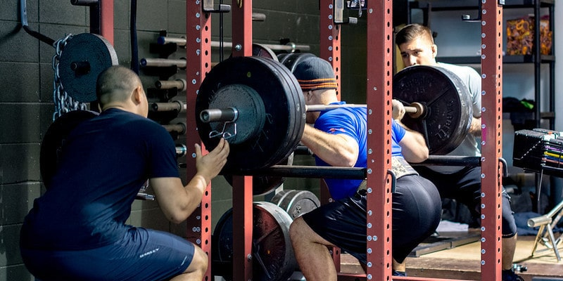 A Man Squatting a Heavy Barbell in a Squat Rack While Being Spotted By Two Other Men