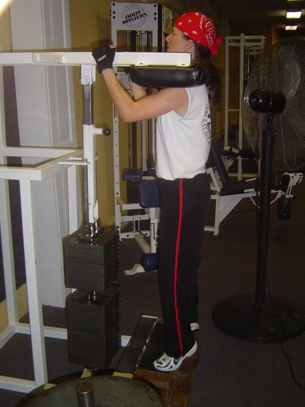A Man Using The Calf Raise Machine