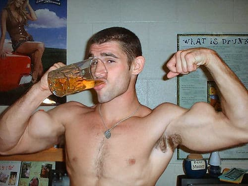 An Athletic Man Drinking a Beer With One Hand and Flexing the Bicep on His Other Arm